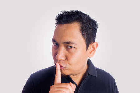 Funny Asian man silly face shushing gesture sssh. Close up face portrait expression Stock Photo