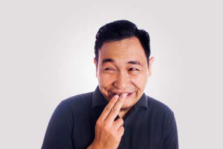 Grappige Aziatische mens die en dwaas gezicht glimlachen denken. Sluit omhoog de uitdrukking van het gezichtsportret Stockfoto