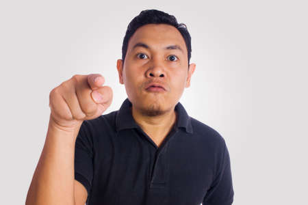 Funny Asian man pointing to camera looked unhappy angry upset. Close up face portrait expression