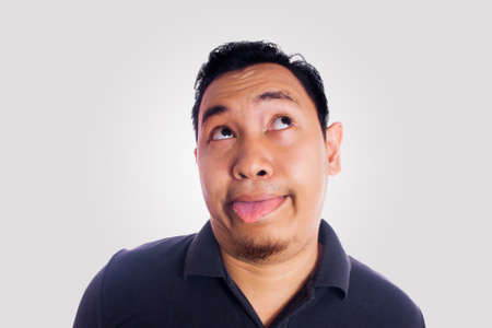 Funny Asian man smiling and thinking silly face with tongue out. Close up face portrait expression