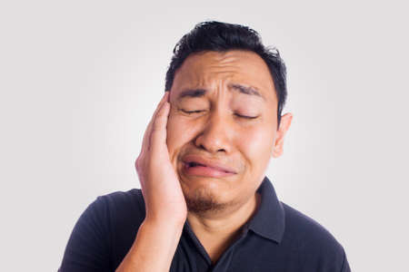 Funny Asian man toothache pain silly face. Close up face portrait expression