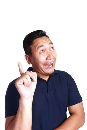 Photo image of funny Asian man smiling thinking and pointing finger for getting an idea, isolated on white