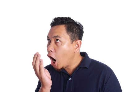 Foto des lustigen asiatischen Mannes, der seinen eigenen schlechten Mundgeruchgeruch, Zahngesundheitsproblem prüft, lokalisiert auf Weiß