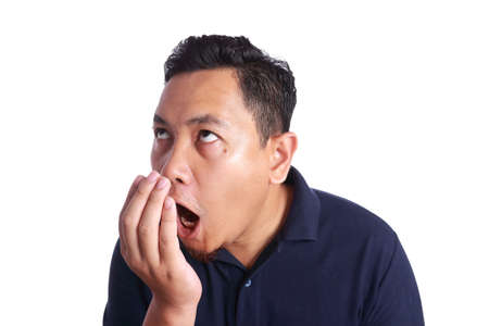 Photo image of funny Asian man checking his own bad mouth smell odor, dental health problem, isolated on white Imagens