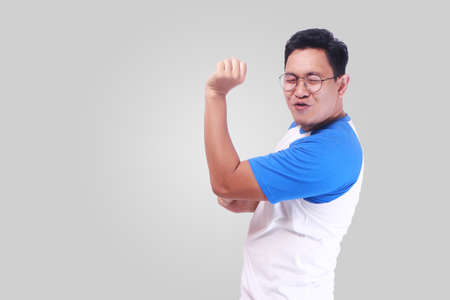 Photo image closeup portrait of a funny young Asian man dancing happily joyful expressing celebrating good news victory winning success gesture, smiling positive excited emotion while standing over grey background