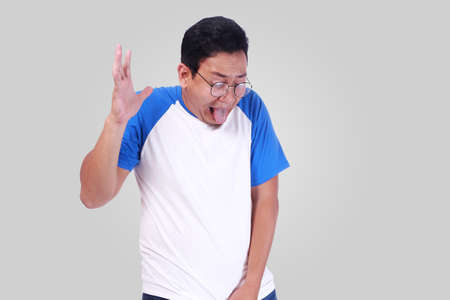 Photo image of funny Asian man crying close his eyes, gesturing as if he is having pain in his sensitive area when pee urinating Reklamní fotografie