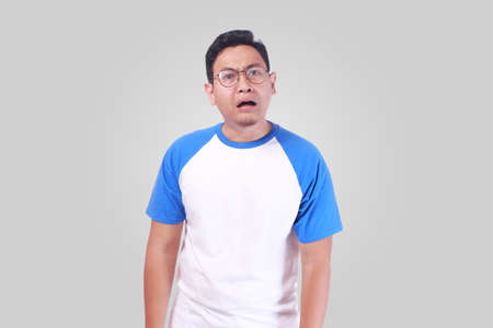 Portrait of upset hopeless young Asian man in white shirt frowning eyebrows and looking at camera with disappointed shocked surprised gesture while standing over grey background Stock Photo