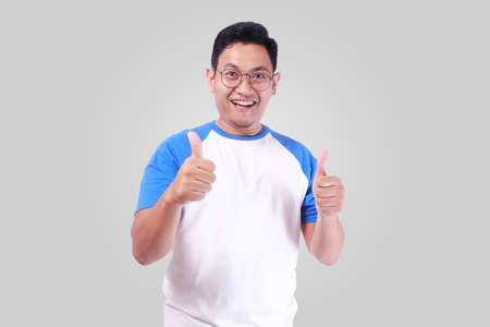 Photo image portrait of funny attractive cute young Asian man in white shirt smiling and showing thumb up sign while standing over grey background
