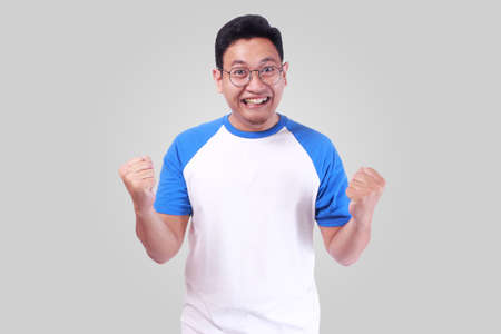 Photo image closeup portrait of excited, energetic, happy, screaming student, business man winning, arms up fists pumped celebrating joy of success victory while smiling and standing over grey backgro