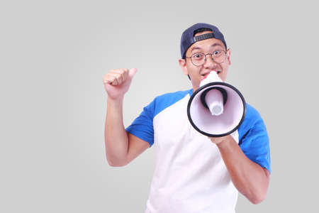 Photo image portrait of funny young attractive Asian man shouting with megaphone, happiness excited calling people promotion concept