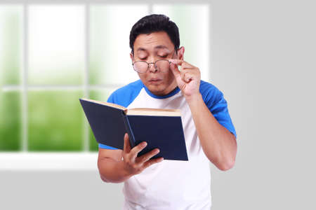 Funny Asian man having trouble reading book with eyeglasses, eye vision problems  Stockfoto