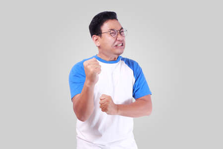 Photo image of funny Asian man showing synical unhappy angry facial expression putting up his fist challenge to fight Stock Photo