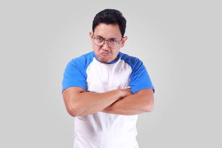 Imagen de la foto del hombre asiático divertido que muestra la expresión facial enojada infeliz synical