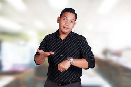 Young attractive Asian man shows unhappy upset facial expression while pointing on his watch, businessman manager angry for his staff to be late Foto de archivo