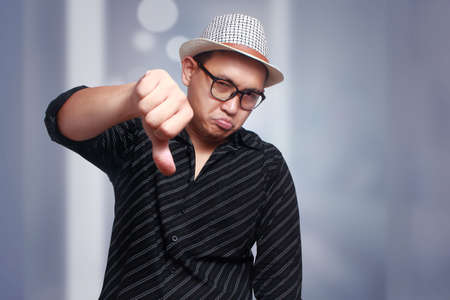 Arrogant Asian man wearing eyeglasses and panama hat mocking with thumbs down gesture Stock Photo