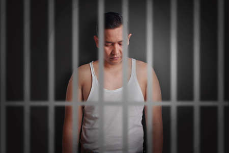 Asian man locked in jail, sad depressed failure concept 版權商用圖片