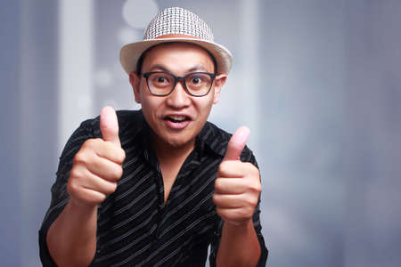 Funny attractive cute Asian man wearing eyeglasses and panama hat smiling with thumbs up