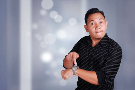 Young attractive Asian man shows unhappy upset facial expression while pointing on his watch, businessman manager angry for his staff to be late Stockfoto