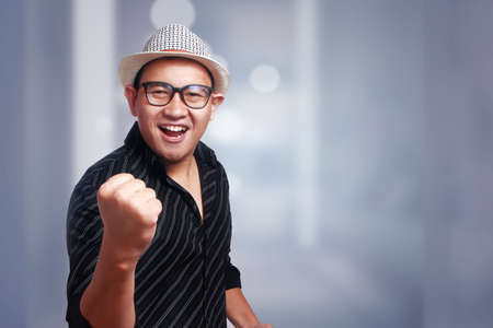 Funny attractive cute Asian man wearing eyeglasses and panama hat smiling winning gesture