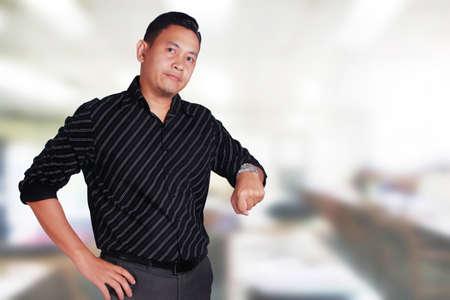 El hombre asiático joven atractivo muestra la expresión facial infeliz del trastorno mientras que señala en su reloj, encargado del hombre de negocios enojado para que su personal llegue tarde