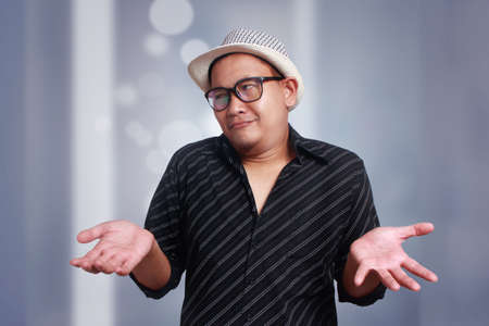 Funny attractive cute Asian man wearing eyeglasses and panama hat showing showing unhappy face, looking side with both of his palms open, shrug shoulder up, showing i don't know gesture