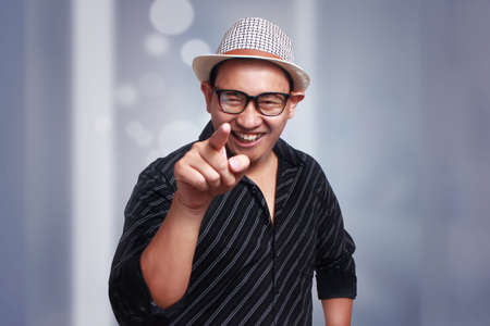 Funny attractive cute Asian man wearing eyeglasses and panama hat smiling and pointing to camera Stock Photo