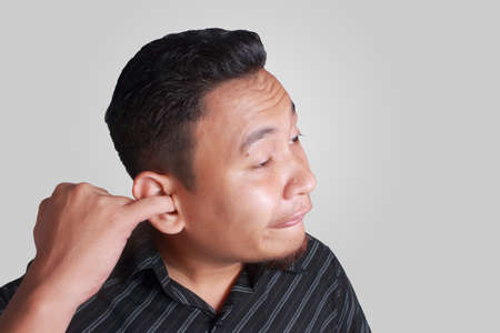 Portrait of young silly and funny Asian man picking his ear