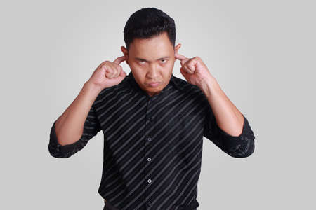 Portrait of young attractive Asian male closing his ears, disturbed to hear noises