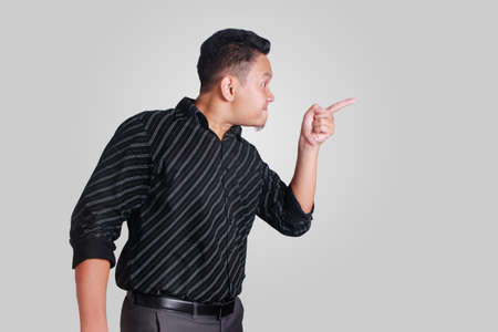 Side view portrait of young Asian man, angry mad boss pointing, isolated on grey