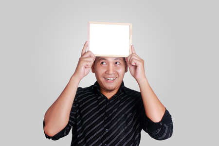 Portrait of young attractive Asian man wearing black shirt, holding and showing small empty copy space whiteboard covering his head, smile happy expression