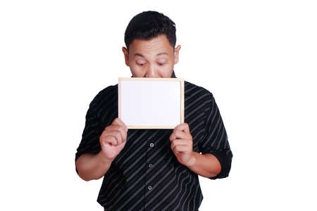 Portrait of young attractive Asian man wearing black shirt, holding and showing small empty copy space whiteboard covering his face, isolated on white Stock Photo