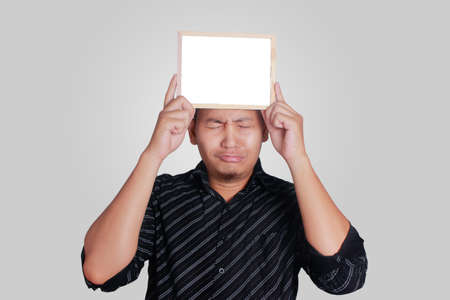 Portrait of young attractive Asian man wearing black shirt, holding and showing small empty copy space whiteboard covering his head, sad crying expression
