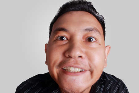 Headshot portrait of funny Asian man showing cynical unhappy angry facial expression, isolated on grey