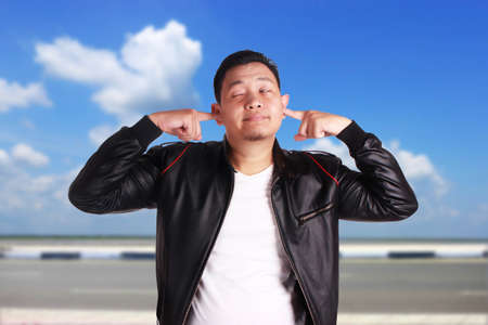 Portrait of young funny Asian man wearing black leather jacket closing his ears as if he is worried afraid to hear of something bad, ignoring gesture, over cloudy blue sky background
