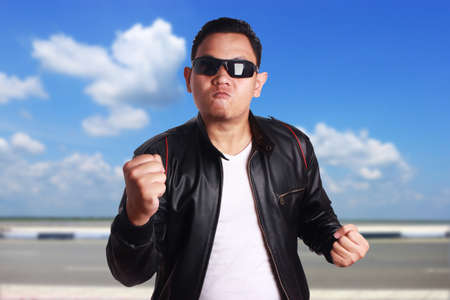 Portrait of funny young Asian Man wearing black leather jacket ready to fight, over cloudy blue sky background