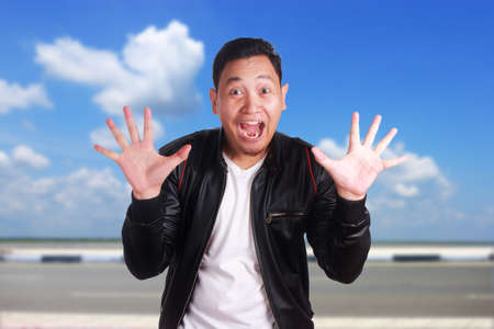 Portrait of young attractive Asian man wearing black leather jacket smiling laughing, over cloudy blue sky background Stock Photo