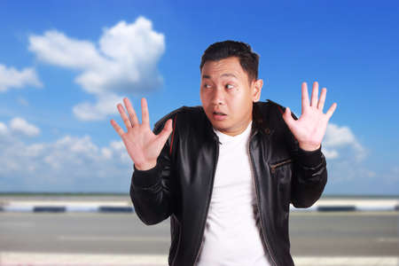 Portrait of funny young Asian man wearing black leather jacket shows hands up surrender gesture, over cloudy blue sky background