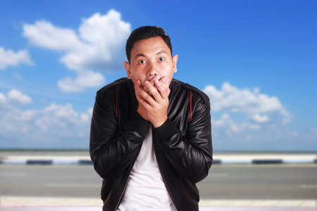 Portrait of attractive young Asian man wearing black leather jacket shocked expression to see something bad, closing his mouth, over cloudy blue sky background
