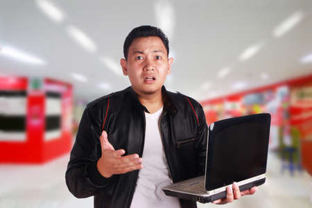 Portrait of young attractive Asian man wearing black leather jacket holding laptop, confused expression Stock Photo
