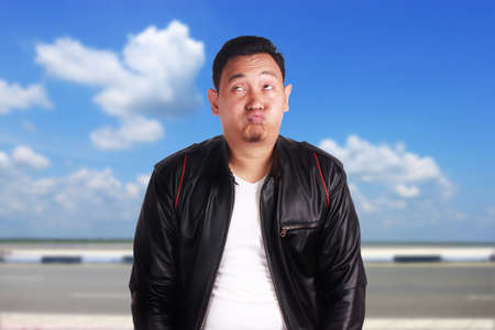 Portrait of attractive young Asian man wearing black leather jacket shows lazy tired annoyed facial expression, over cloudy blue sky background