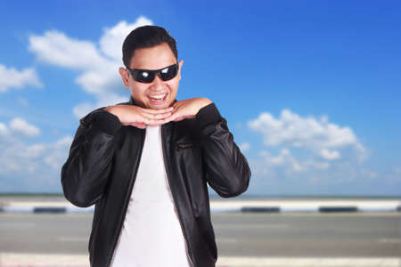 Portrait of funny young Asian man doing flirtatious feminine act, hands under chin, over cloudy blue sky background  Stock Photo
