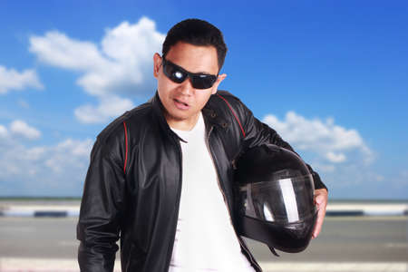 Portrait of young attractive Asian men wearing black leather jacket and sunglasses smiling mocking, happy racer biker rider over cloudy blue sky outdoor scenery background