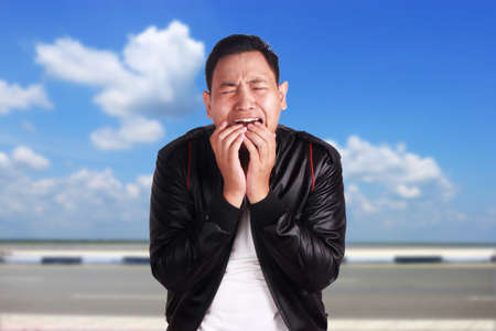 Asian man wearing black leather jacket crying, sad depression frustration hopeless expression over cloudy blue sky background
