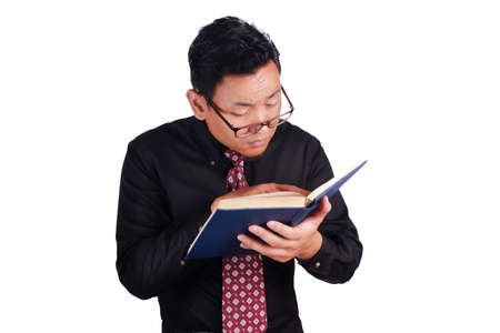 Portrait of young businessman wearing eyeglasses holding and reading a book, eye sight problem