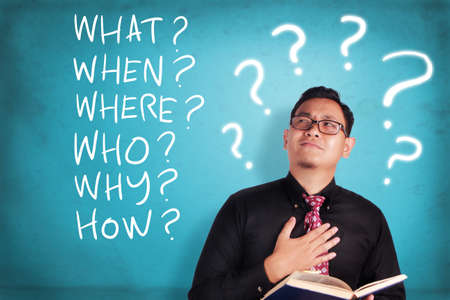 Portrait of young businessman holding a book and thinking basic questions, what when where who why how