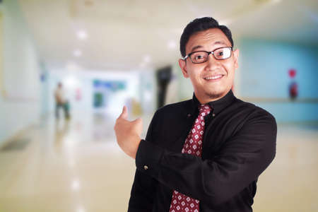 Portrait of happy young Asian businessman smiling and pointing something behind him, successful business people concept, over blurred background