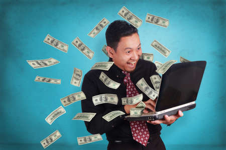 Portrait of young Asian businessman typing on laptop, happy smiling expression, money business online profit concept, over blue wall background
