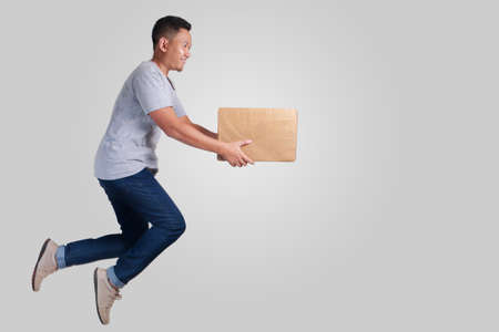 Levitatie-koerier, aantrekkelijke jonge Aziatische man leveren pakket tijdens het wandelen in de lucht
