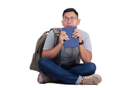 Giovane libro di lettura asiatico attraente dello studente mentre sedendosi sul pavimento, isolato sul bianco, guardante su e pensante gesto
