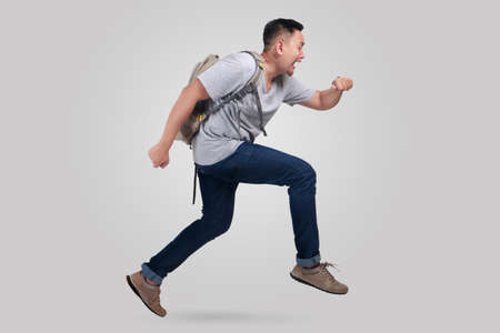 Attractive young Asian man worried and running fast to be late
